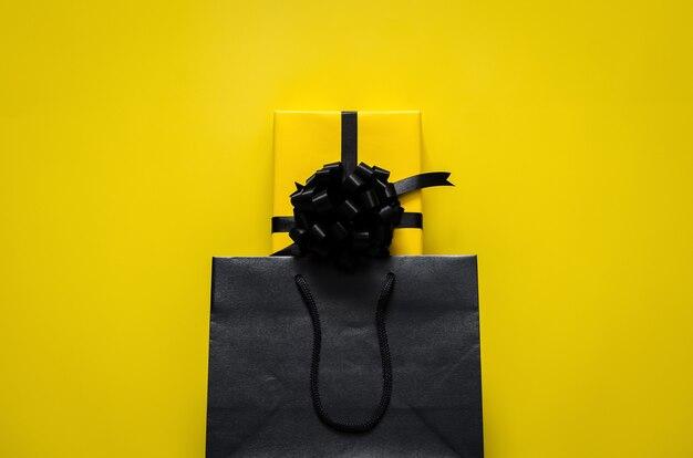 Желтая подарочная коробка помещается в черную хозяйственную сумку с желтым фоном. черная пятница и концепция дня подарков.