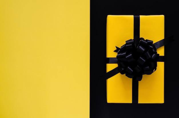 Желтая подарочная коробка с черной лентой надевается на черный и желтый фон. черная пятница и концепция дня подарков.