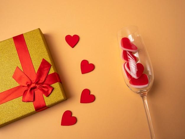 Желтый подарок с лентой в виде узла-бабочки лежит рядом с четырьмя красными сердечками и бокалом с красными сердечками на оранжевом фоне.
