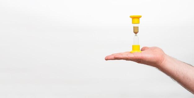 男の手の中の黄色い砂時計は、コピー スペースで白い背景に分離します。