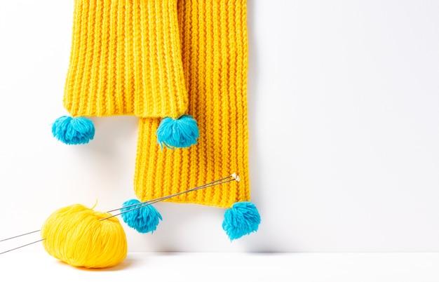 黄色のニットスカーフ、その隣に白い背景に編み針が付いた黄色の糸。