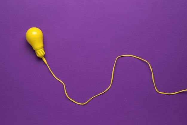 紫色の背景の長い黄色のワイヤー上の黄色の電球。ミニマリズム。フラットレイ。