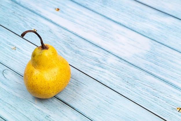 黄色の梨の木が青い木製の背景の上にあります。夏のコンセプト。