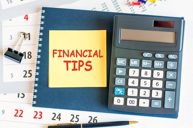 텍스트 금융 팁과 계산기가있는 노란색 종이가 메모장에 누워 노트북과 펜이 문서 페이지 금융 개념 선택적 초점에 배치됩니다