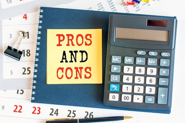 장단점이 있는 노란색 종이와 계산기가 메모장에 놓여 있습니다. 노트북과 펜은 문서 페이지에 배치됩니다. 금융 개념입니다. 선택적 초점