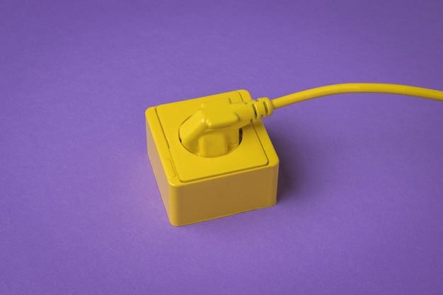 보라색 배경에 노란색 콘센트에 연결된 노란색 전원 코드. 세련된 디자인. 전기 제품이 연결된 장소.