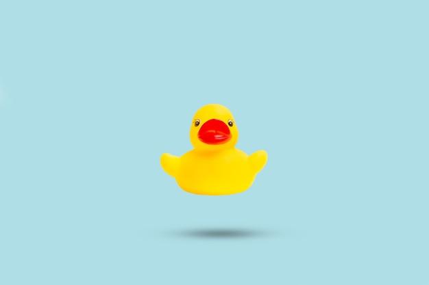 Желтая резиновая игрушечная утка, плавающая на голубом