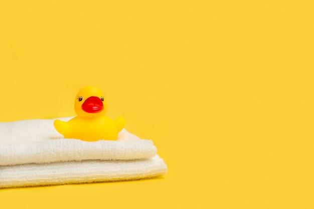 Желтая резиновая игрушечная утка на белых полотенцах