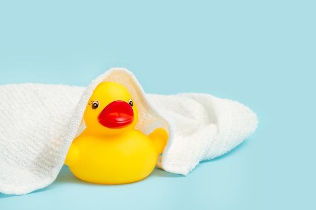 Желтая резиновая игрушка-утенок с полотенцем на нем и на голубом