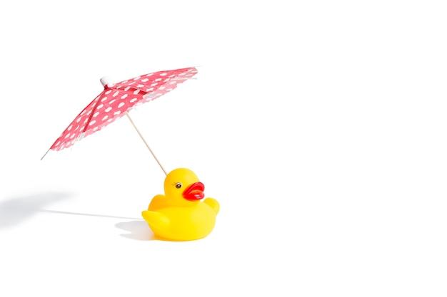 Желтая резиновая игрушка утка с зонтиком на белом