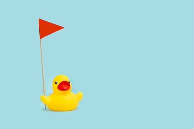 Желтая резиновая игрушечная утка с красным вымпелом на голубом