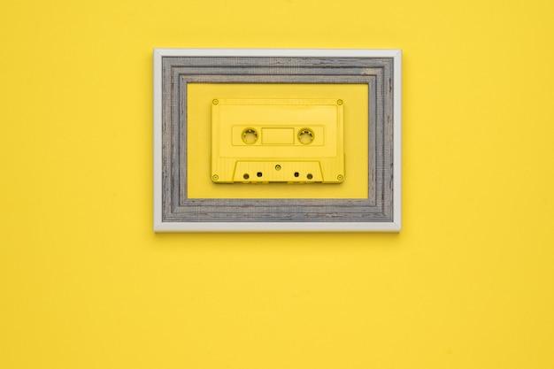 노란색 배경에 프레임에 노란색 테이프 카세트. 플랫 레이.