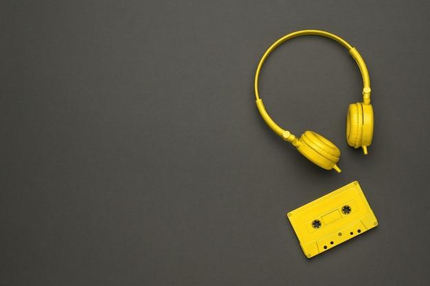 검정색 배경에 노란색 테이프 레코더와 노란색 헤드폰. 컬러 트렌드. 플랫 레이.