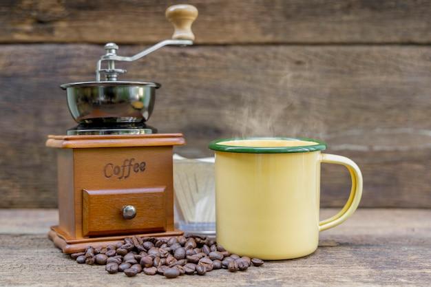 木製のテーブルにコーヒーグラインダーとコーヒー豆とホットコーヒーの黄色の錫カップ。