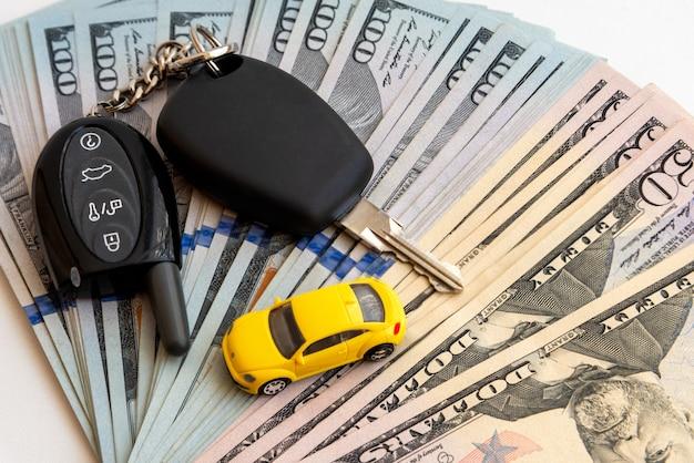 노란색 장난감 자동차와 흰색 표면에 미국 달러의 스택. 신용으로 자동차를 구입하십시오. 자동차 구매를위한 저축.