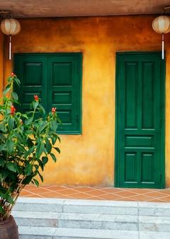 Желтая стена с зеленой дверью и окном с китайскими фонариками. красивая старая архитектура древнего города хойан. вьетнам.
