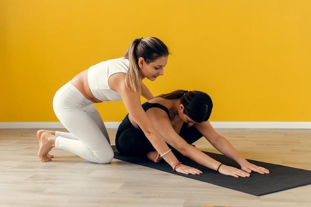 Учитель йоги помогает вам наклониться вперед