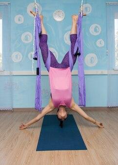 Женщина-йога в спортивной одежде выполняет перевернутую асану в гамаке в студии