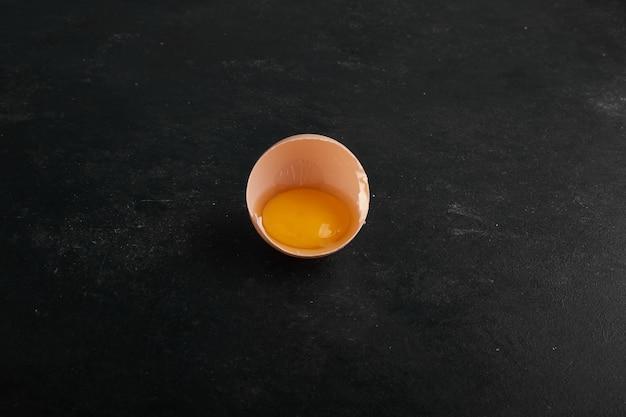 中央の黒い表面にある卵殻の中の卵黄。