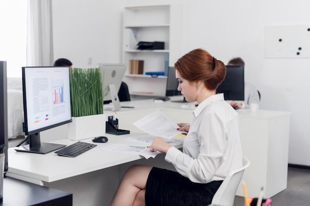 Молодой бухгалтер в офисе изучает бухгалтерскую финансовую налоговую отчетность в офисе коммерческой компании. монитор мокапа.