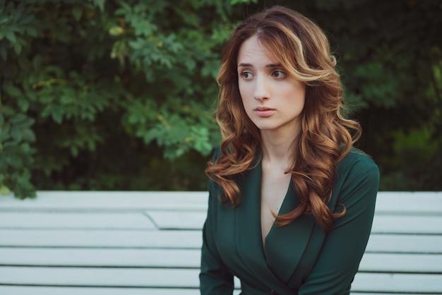 긴 곱슬 머리를 가진 젊은 성인 아름다운 갈색 머리 여자는 녹색 드레스에 벤치에 앉아있다
