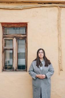 窓のある古い壁の近くの灰色のコートを着た若い大人の女の子
