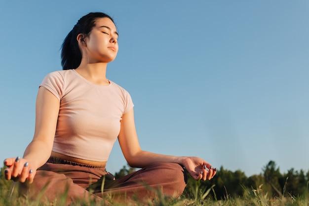 Молодая взрослая девушка азиатской внешности сидит на лужайке и медитирует.