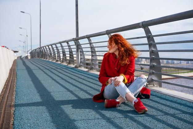 赤いジャケットのブルージーンズと赤いスニーカーを着た若い大人の赤毛の女性が歩道に座っています...