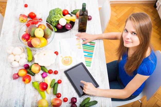 Молодая взрослая женщина с помощью планшетного компьютера узнает о пищевой ценности фруктов
