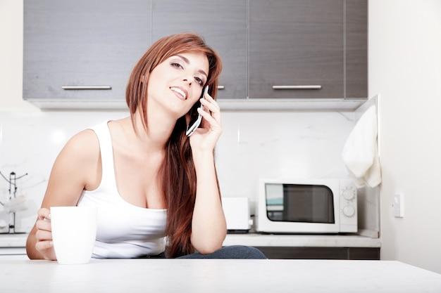 Молодая взрослая женщина, сидя на кухне во время разговора по смартфону.