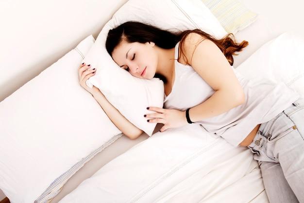 Молодая взрослая женщина спит на кровати.