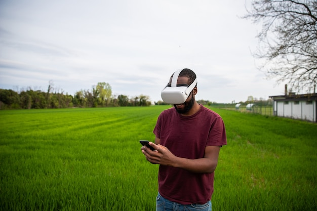 젊은 아프리카 계 미국인 소년이 야외 필드에서 스마트 폰으로 vr 헤드셋을 사용합니다.
