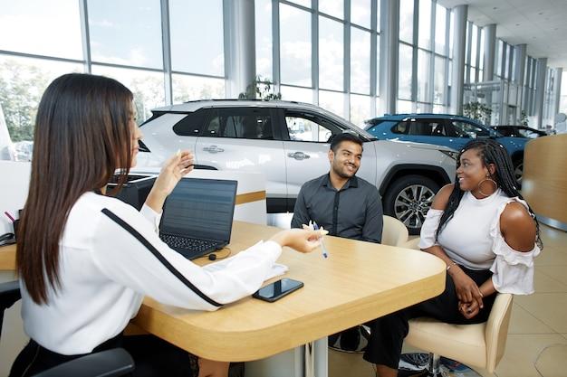 車の販売のためにエージェントと通信する若いアフリカ系アメリカ人のカップル
