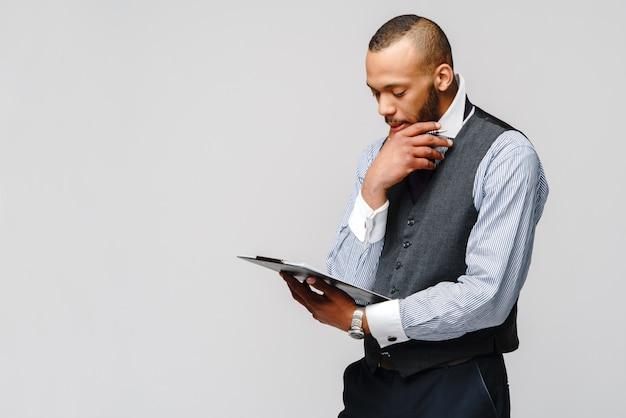 Молодой человек афроамериканца держа простые таблетку и ручку таблицы.