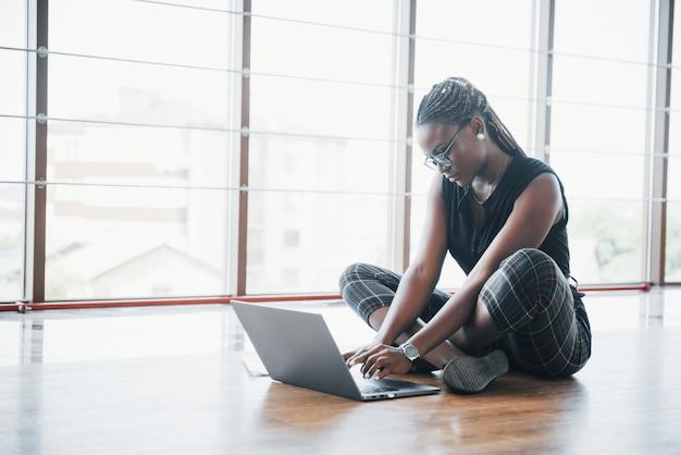 若いアフリカ系アメリカ人女性はラップトップコンピューターに満足しています。