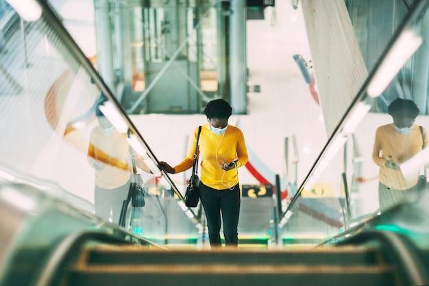 보호 의료 마스크를 쓴 젊은 아프리카 여성이 지하철의 에스컬레이터를 타고 헤드폰으로 음악을 듣습니다. 현대 기술, 유행병, 사회적 거리.