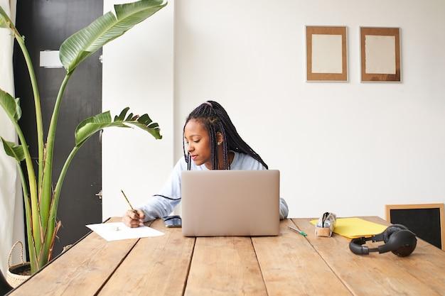 Молодая афроамериканка работает одна, она пользуется ноутбуком, а также делает заметки в блокноте ...