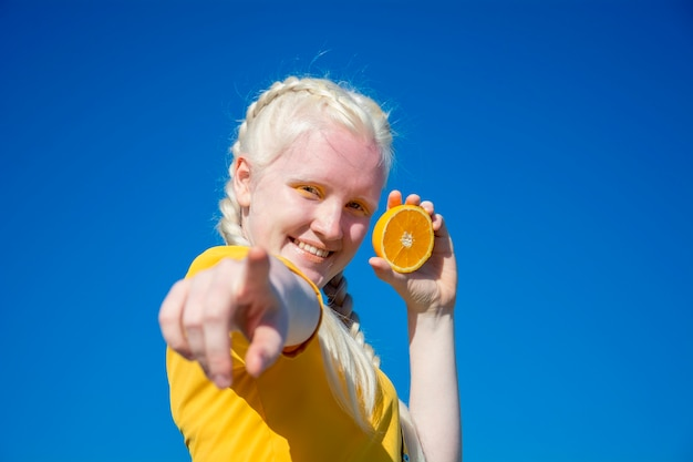 若いアルビノの女性がカメラに指を向け、青い空を背景にオレンジのスライスを片手に持っています