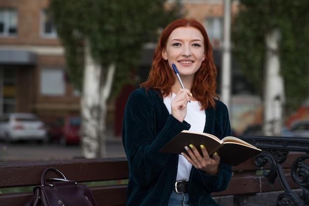 Молодая и привлекательная девушка рыжая кавказская сидя на скамейке, держа блокнот и думая.