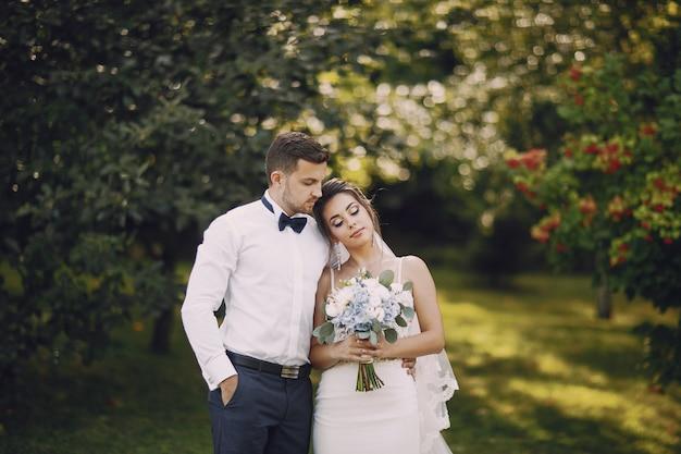 부케와 여름 공원에 서있는 젊고 아름다운 신부와 그녀의 남편