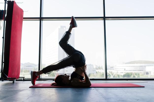 젊고 아름다운 여성이 체육관에서 바벨과 함께 훈련합니다. 훈련을위한 요소로 포즈