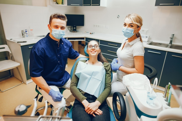 Молодая и красивая девушка лечит зубы с помощью дантиста, а помощник помогает ему
