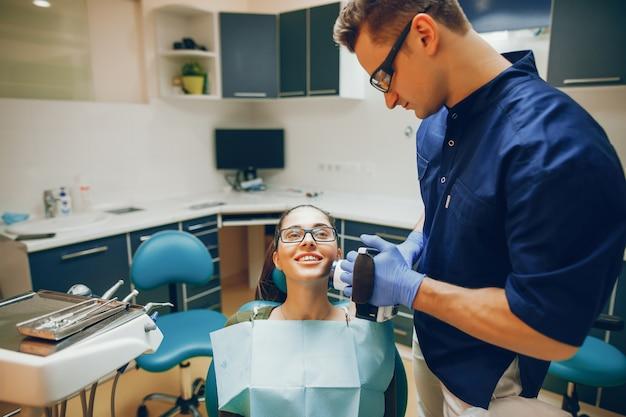 Молодая и красивая девушка лечит зубы стоматологом