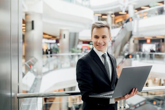 若くて陽気な男は、彼の手でラップトップを保持し、モールで黒いスーツを着ています