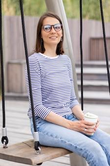 若くて自信のある女性ブロガーまたはマーケティング担当者が休んでいて、女性が待っているブランコに乗っています