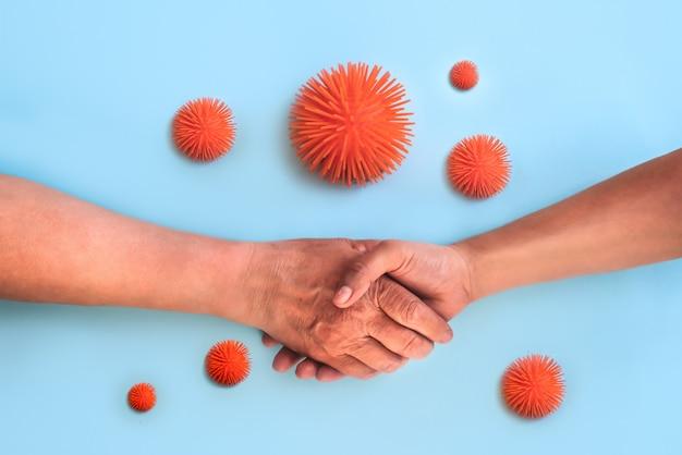 악수를하는 어린 어른의 손에 바이러스가 날아 다니고 있습니다. 위험한 악수.