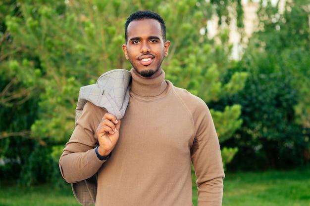 サマーパークでスタイリッシュなスーツを着た若くてハンサムなスタイリッシュなモデルのアフリカ系アメリカ人男性。写真撮影でポーズをとるラテンアメリカのヒスパニック系ビジネスマン黒人の男