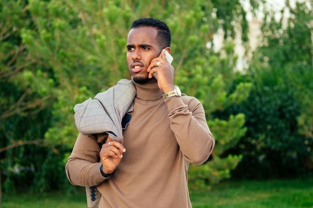 サマーパークでスタイリッシュなスーツを着た若くてハンサムなスタイリッシュなモデルのアフリカ系アメリカ人男性。ラテンアメリカのヒスパニック系ビジネスマンの黒人男性は、電話と電話を使用します。