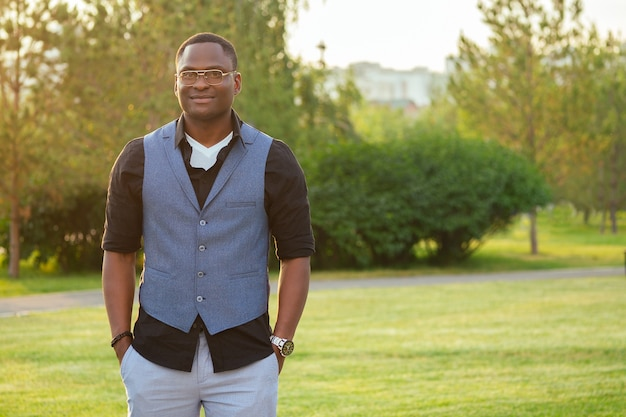 Молодой и красивый стильный афроамериканец в стильном костюме в летнем парке. латиноамериканец латиноамериканец бизнесмен черный парень идет после работы в офисе