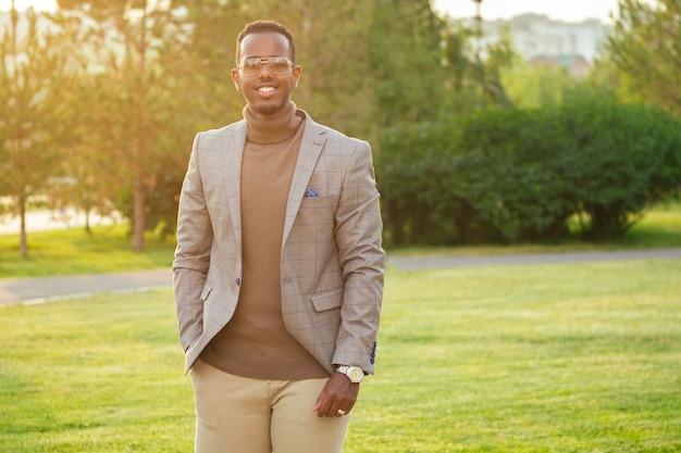 Молодой и красивый стильный афроамериканец в стильном костюме в летнем парке. латиноамериканский латиноамериканский бизнесмен черный парень идет после работы в офисе.